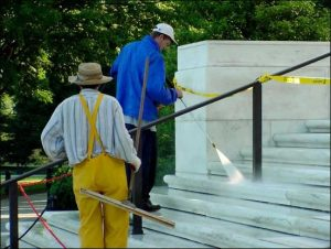 Workers power-washing stairs